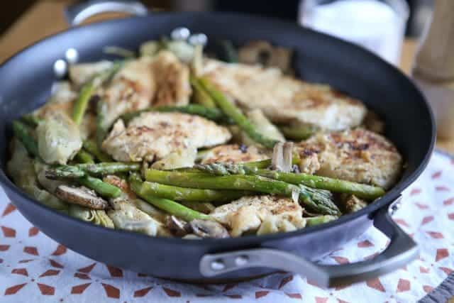 skillet with chicken, artichokes, mushrooms, and asparagus