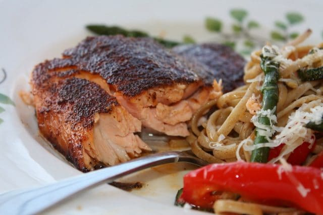 piece of broiled salmon on white plate with fork and pasta with vegetables