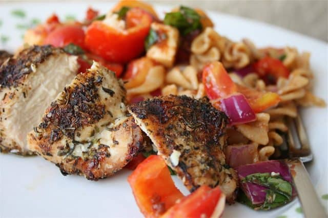 plate of herb grilled chicken with side of pasta salad with various vegetables