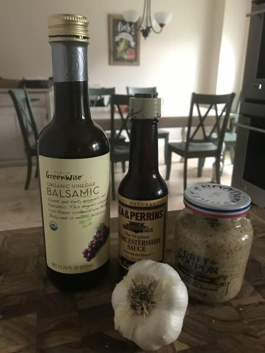 ingredients for london broil marinade including balsamic vinegar bottle, worcestershire sauce bottle, jar of grey poupon country dijon and bulb of garlic