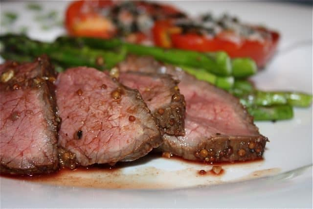 sliced london broil on white plate with asparagus and tomatoes in background