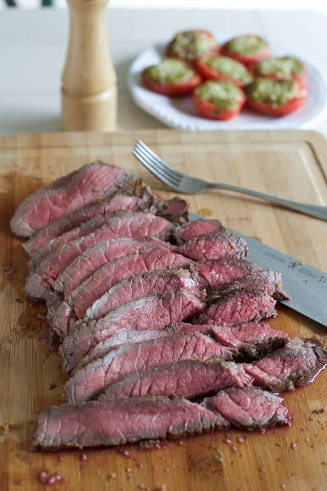 London broil on a cutting board sliced thin with roasted pesto tomatoes in background