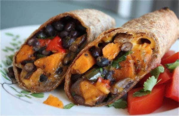two halves of sweet potato and black bean burrito on a plate