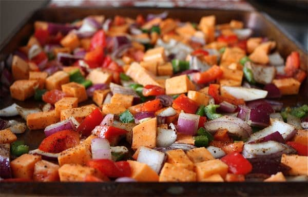 sheet pan of sweet potatoes and vegetables ready to be roasted