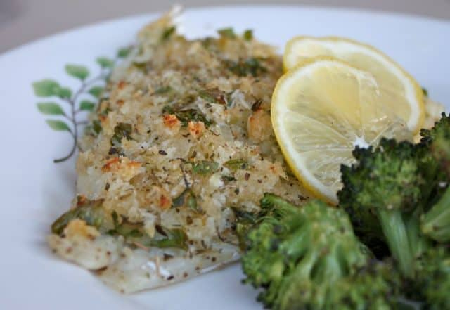 breaded and herbed baked fish on plate with broccoli and lemon