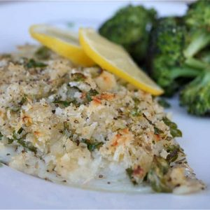 baked breaded fish on a plate with lemon