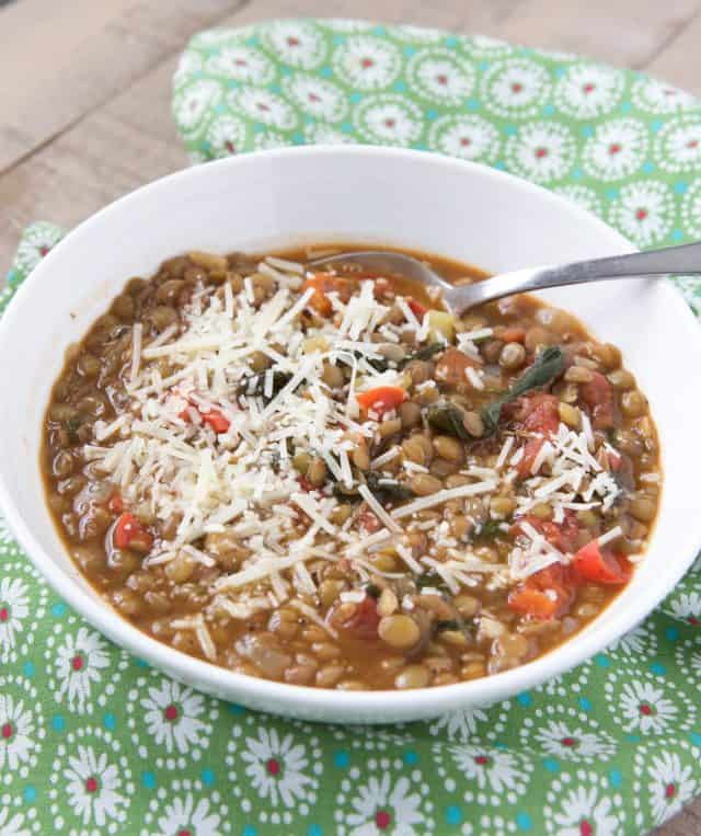 lentil soup sprinkled with parmesan reggiano cheese in a white bowl on a green napkin