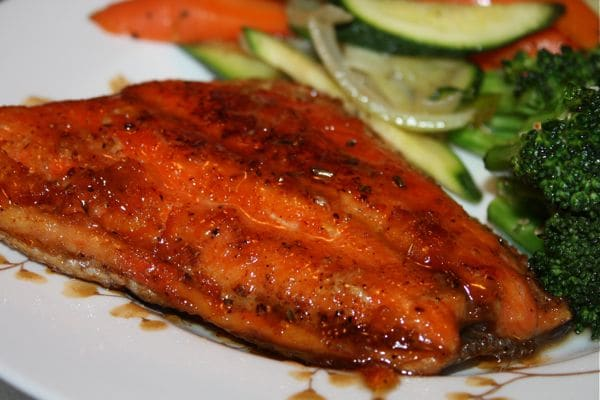 plate of orange glazed salmon with vegetables on the side