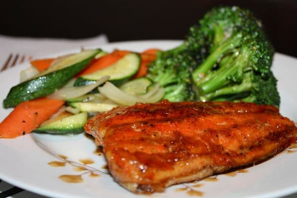 plate of orange glazed salmon with carrots, white onions, zucchini, and broccoli