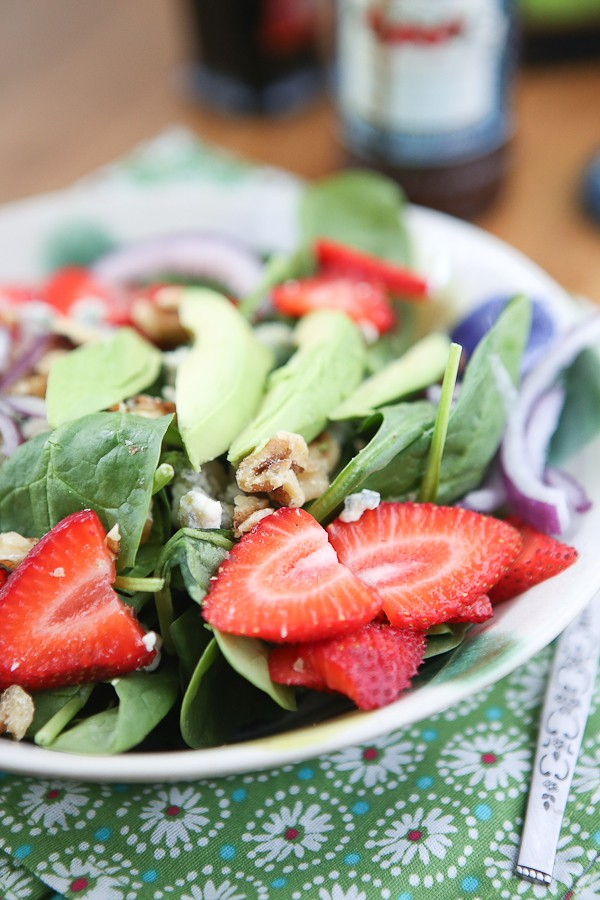 bowl of spinach salad in a bowl topped with strawberries, avocado slices, and walnuts