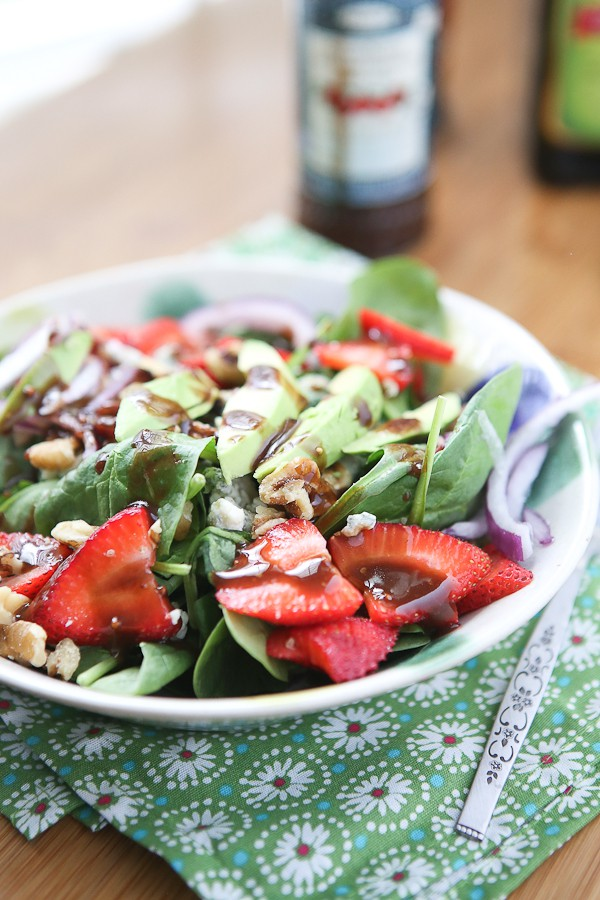 bowl of spinach salad in a bowl topped with strawberries, avocado slices, walnuts, and a raspberry balsamic vinaigrette dressing