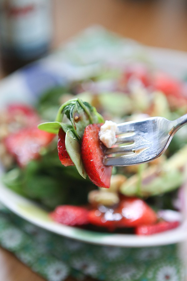 close up of fork with spinach, strawberry, and cheese covered in raspberry balsamic vinaigrette