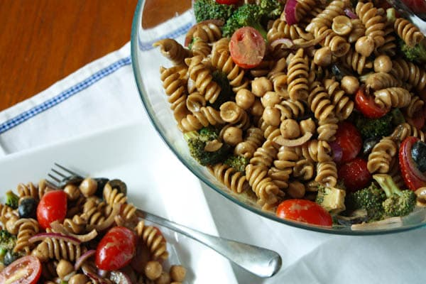 pasta salad with cherry tomatoes, olives, red onions, and broccoli in a bowl and on a plate with a fork
