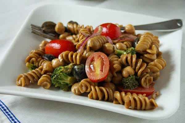 pasta salad with cherry tomatoes, olives, red onions, and broccoli on a plate with a fork