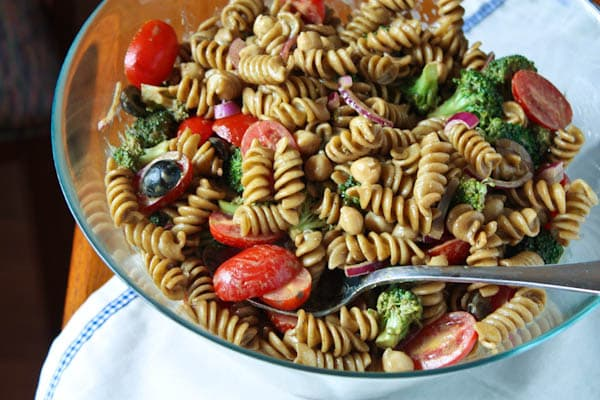 pasta salad with cherry tomatoes, olives, red onions, and broccoli in a bowl