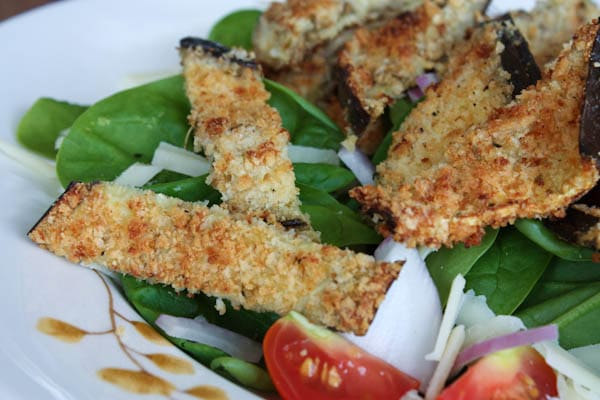 plate of spinach salad topped with cherry tomatoes, red onion, shredded cheese, and baked breaded eggplant