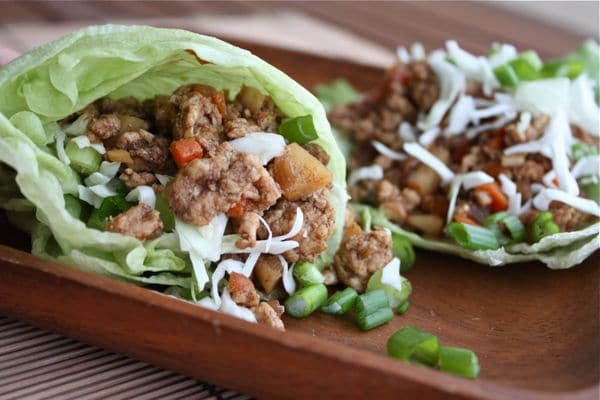 wooden plate with lettuce wraps stuffed with ground turkey, water chestnuts, and chopped green onion