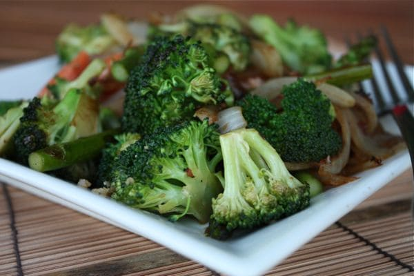 plate with salmon and veggie stir fry, focusing on the broccoli with a fork resting on the plate