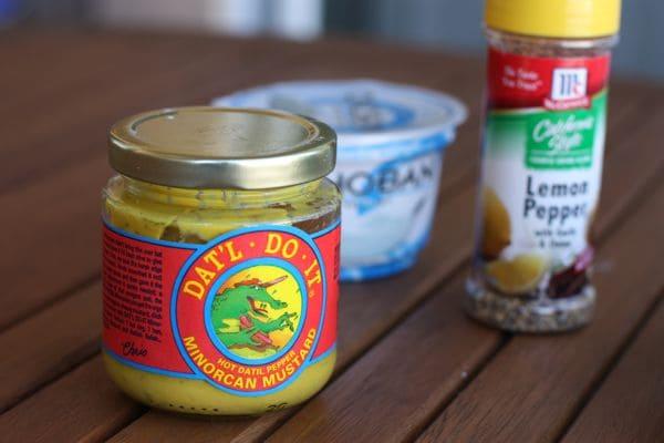 "jar of ""Dat'l Do It"" mustard, Chobani plain Greek yogurt, and container of lemon pepper seasoning"