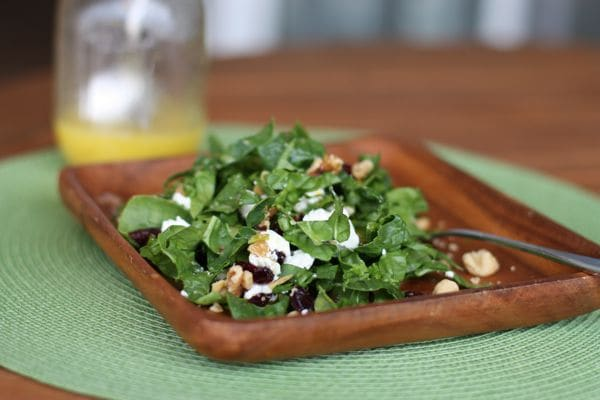plate of kale topped with dried cranberries, toasted walnuts, crumbled goat cheese, and vinaigrette