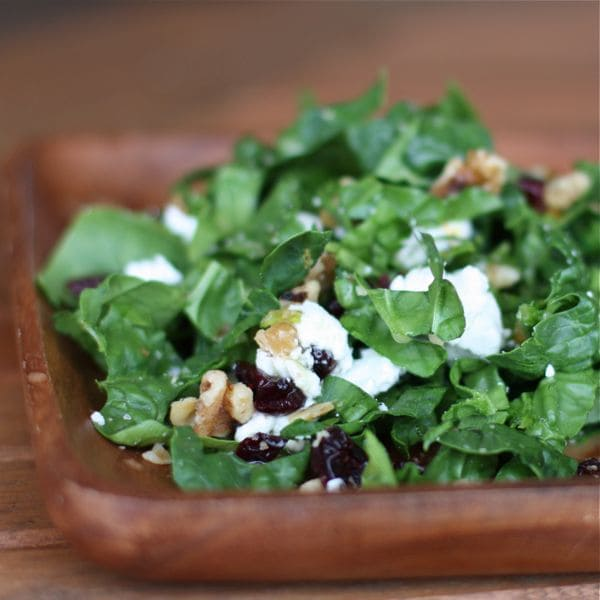 plate of kale topped with walnuts, cranberries, and goat cheese
