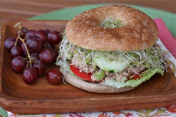 wooden plate with a whole wheat bagel stuffed with tuna salad, sliced tomatoes, lettuce, sliced cucumber, and alfalfa sprouts with a side of red grapes