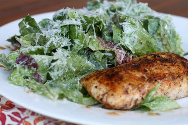 bowl of greens tossed with caesar dressing and topped with shredded parmesan cheese and blackened mahi