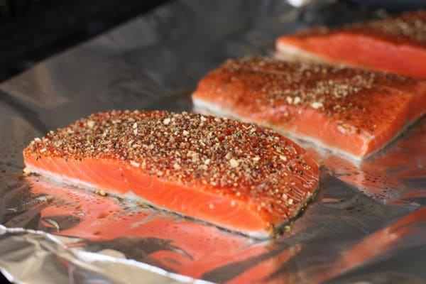raw salmon covered with seasonings on a baking sheet covered in aluminum foil