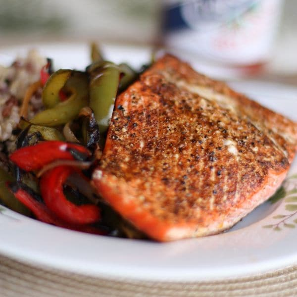 plate of blackened salmon alongside grilled green and red bell peppers with a side of rice