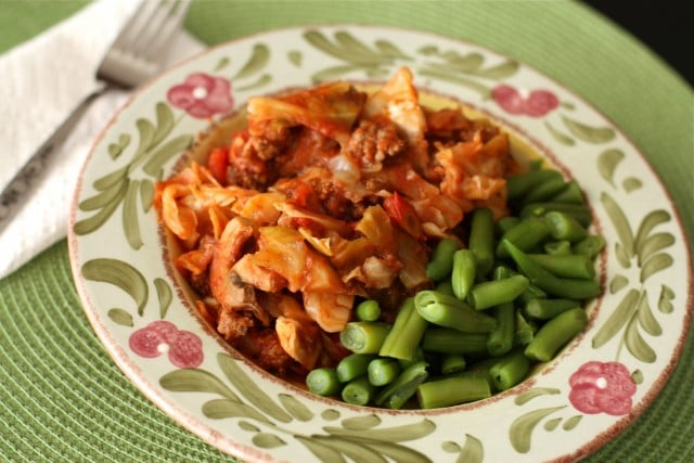 plate of cabbage with ground turkey covered in red sauce and a side of green beans