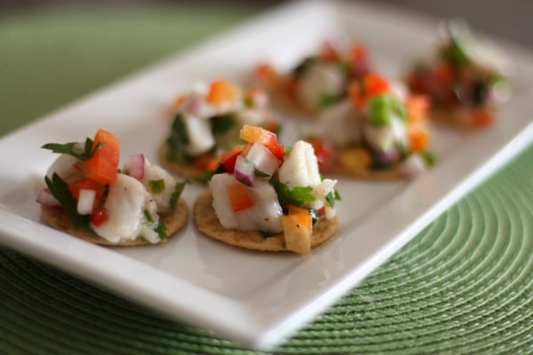 plate of 6 crackers topped with ceviche mix of diced white fish, red onions, tomatoes, and cilantro