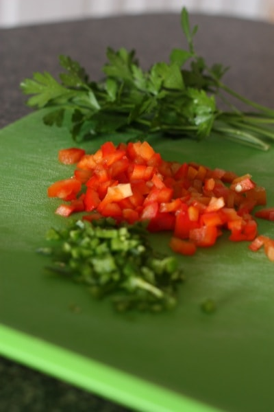 chopped red bell pepper and cilantro chopped on a green cutting board