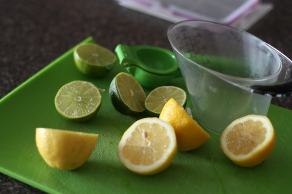 lemons and limes cut in half on a green cutting board, prepared to be juiced