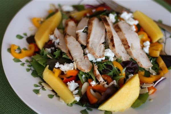 plate of mixed greens topped with yellow and orange bell peppers, sliced mango, goat cheese, almonds, and chicken