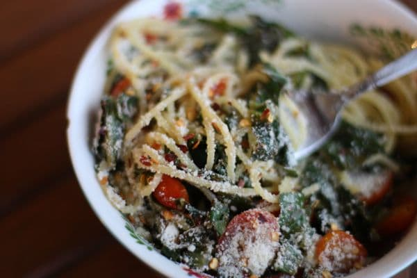 A quick and healthy Quinoa Spaghetti with Garlicky Greens and Tomatoes dish for a vegetarian option at dinner.