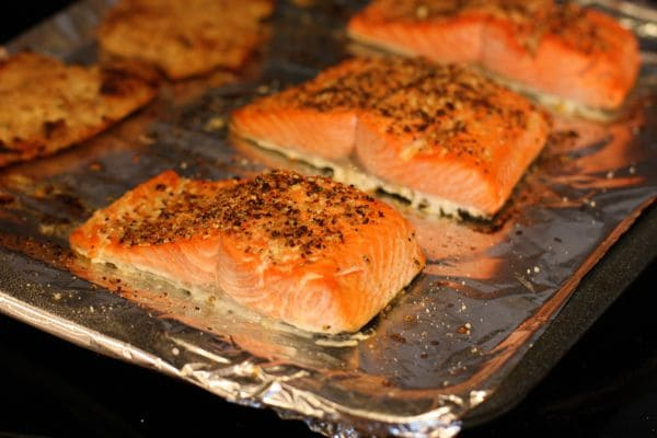 salmon covered in seasonings on a baking sheet covered with aluminum foil