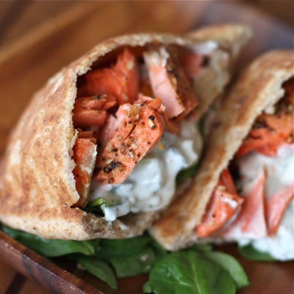 Broiled salmon gyros are a healthy twist on traditional lamb or chicken gyros, using broiled salmon, fresh veggies and Greek yogurt dip tzatziki sauce.