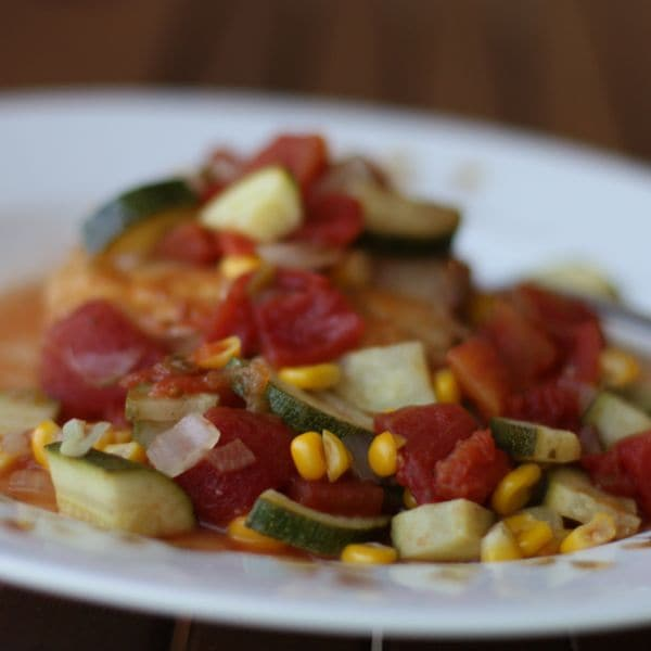 plate of piece of mahi mahi covered with tomatoes, zucchini, and corn