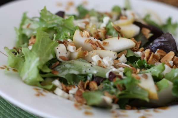plate of salad with pear slices, granola, and greek yogurt poppyseed dressing
