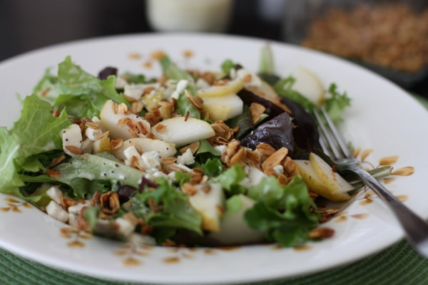 plate of salad topped with pear slices, granola, and greek yogurt poppyseed dressing
