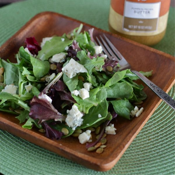 plate of mixed greens topped with pepitas and bleu cheese next to pumpkin butter vinaigrette