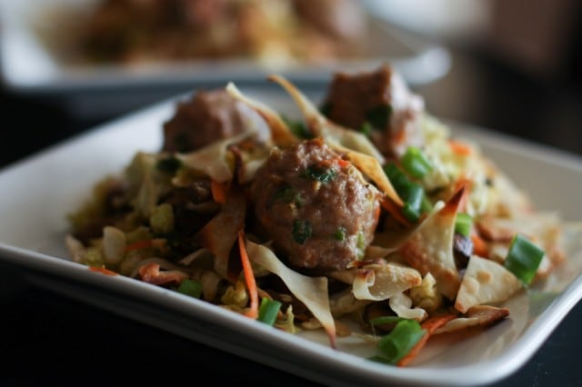 plate of chopped cabbage topped with mushrooms, carrots, green onions, wonton crisps, and meatballs