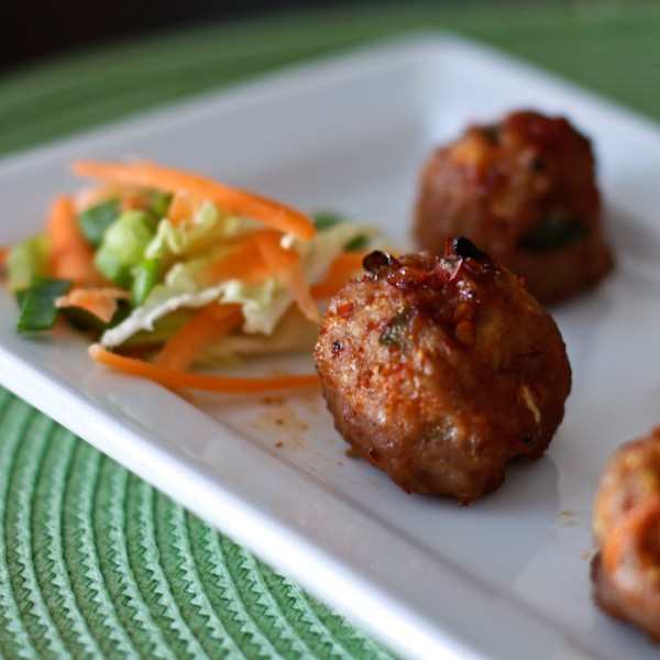 turkey meatballs covered in a chili garlic glaze on a plate with a mini side salad