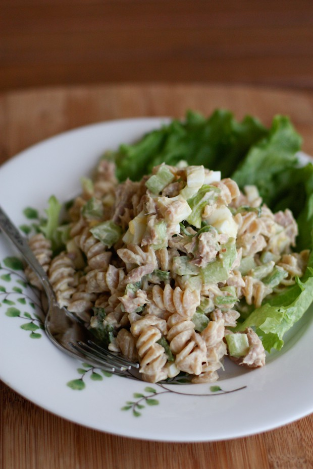 white plate with rotini pasta and tuna pasta salad over lettuce