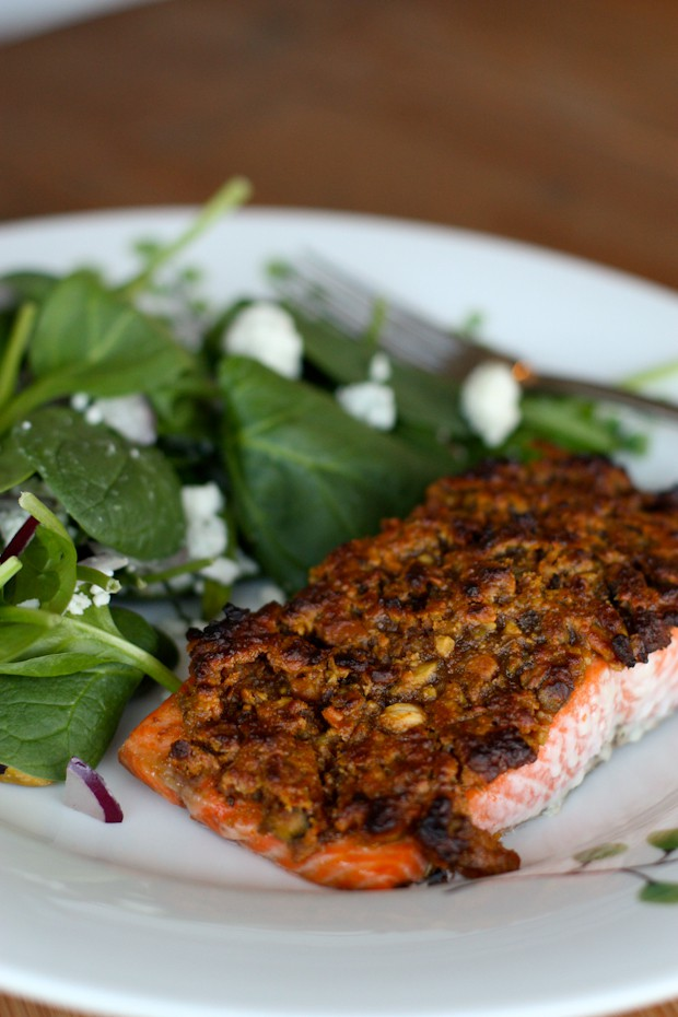 pistachio crusted salmon on white plate with spinach salad