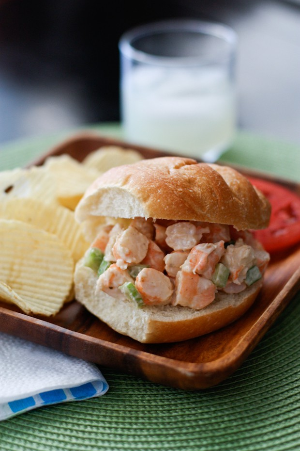 shrimp salad in a bakery roll on a wooden plate with potato chips