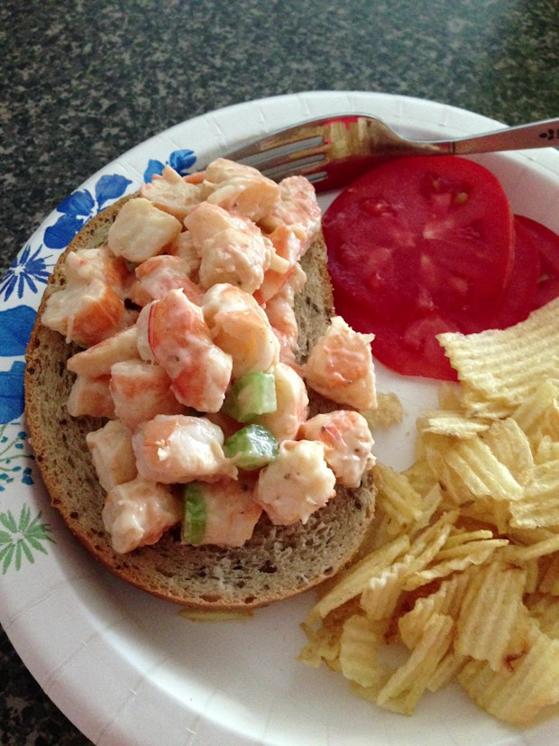 open faced shrimp salad sandwich on rye bread on a plate with sliced tomato and potato chips