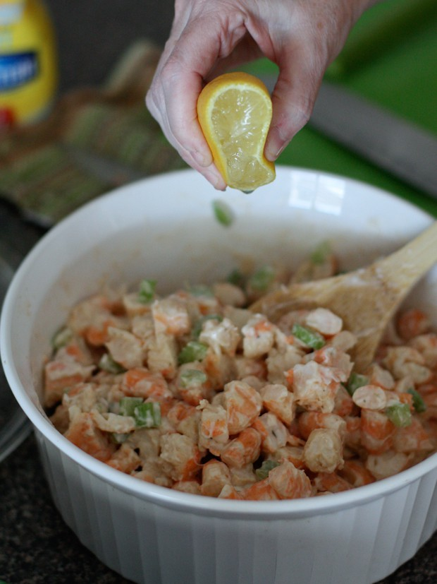 hand squeezing lemon into a white bowl with fresh shrimp salad