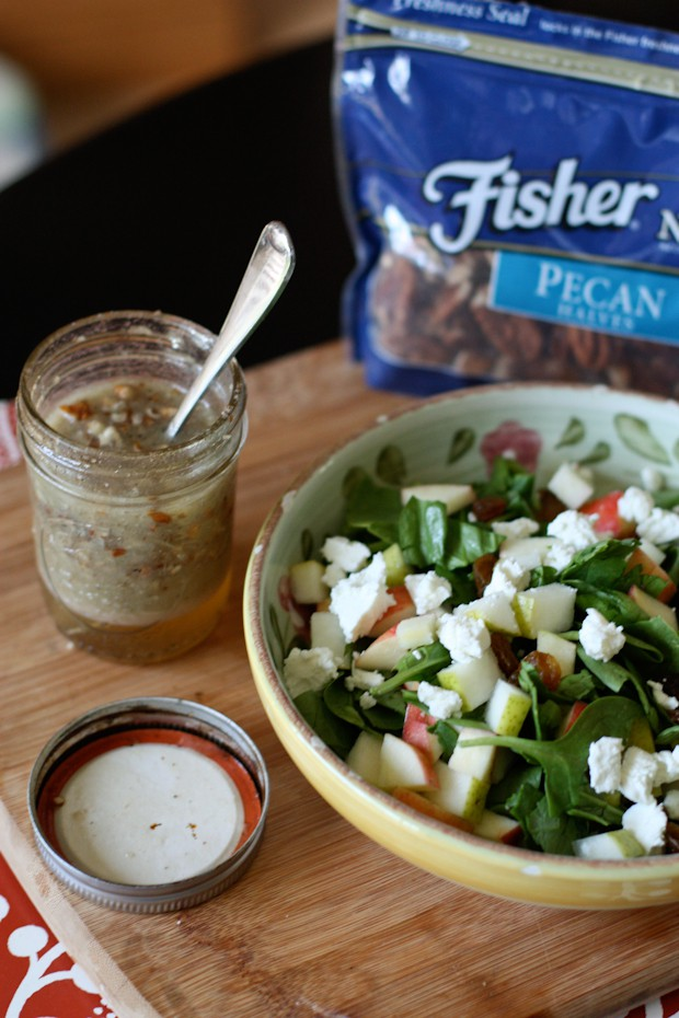 bowl of spinach salad topped with feta cheese and apple slices next to mason jar of pecan vinaigrette with spoon in it and a bag of Fisher pecan halves in the background