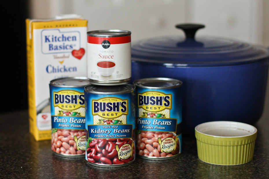 two cans of Bush's pinto beans, can of Bush's kidney beans, can of Publix tomato sauce, container of chicken stock, and a blue dutch oven